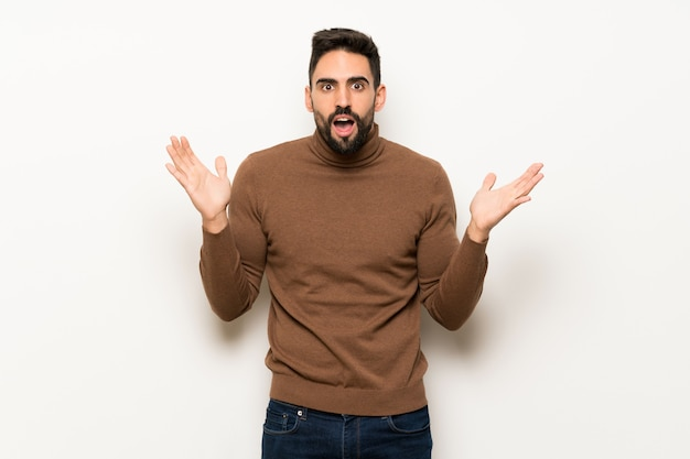 Handsome man over white wall with surprise and shocked facial expression