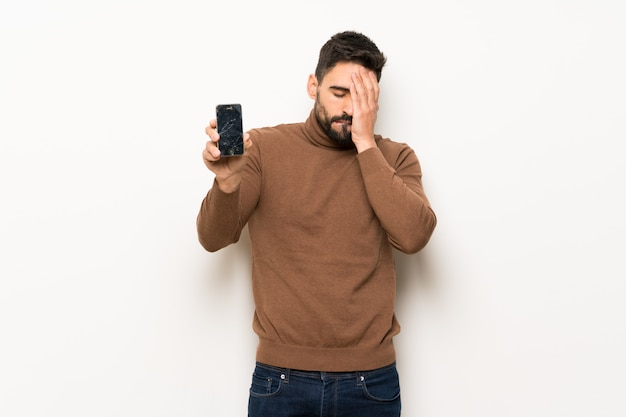 Handsome man over white wall with troubled holding broken smartphone
