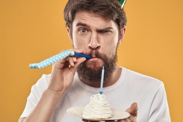 Красивый мужчина с бородой и в кепке празднует день рождения на желтом фоне.