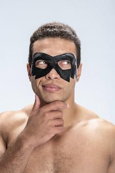 Красивый мужчина с черной маской вокруг глаз потирает подбородок
