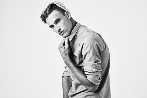 彼の襟の自信を保持しているシャツのファッショナブルな髪型を持つハンサムな男