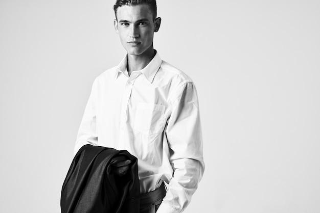手にジャケットを着たハンサムな男白いシャツのポーズモデル