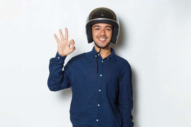 白い背景の上の親指をokジェスチャーを示すオートバイのヘルメットを持つハンサムな男