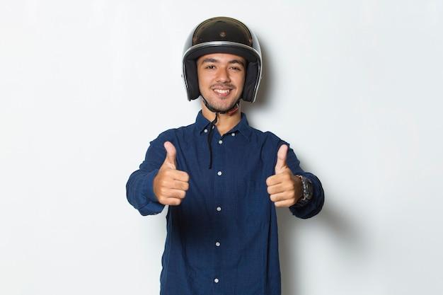 오토바이 헬멧을 쓴 잘생긴 남자는 흰색 바탕에 엄지손가락을 치켜든다