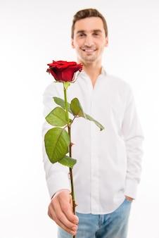 ポケットに手をつないで赤いバラを持つハンサムな男