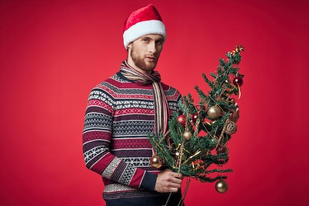 彼の手に木を持つハンサムな男は、休日の楽しい赤い背景を飾ります