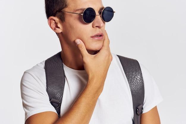 背中にバックパックを持ったハンサムな男がtシャツを着て両手でジェスチャーし、眼鏡をかけている肖像画のトリミングされたビュー