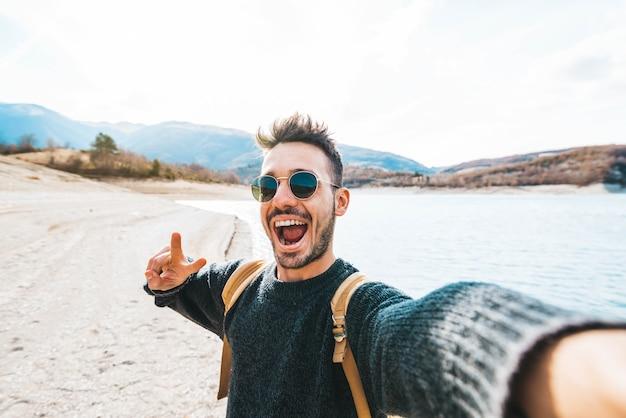 야외 셀카를 찍는 배낭을 가진 잘생긴 남자 젊은 등산객은 카메라를 보며 웃고 있는 산을 여행합니다.