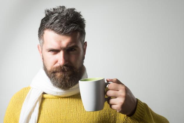 コーヒーやお茶を楽しんでいるひげと口ひげを持つハンサムな男。手に温かい飲み物とカップを保持している真面目な男-飲み物とレジャーの概念。寒い時期の温かい飲み物。カフェを宣伝するためのスペースをコピーします。