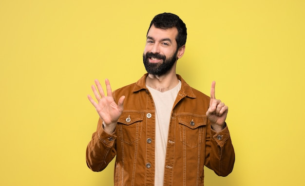 Handsome man with beard counting six with fingers