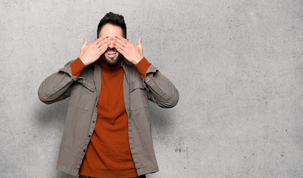 Handsome man with beard covering eyes by hands.