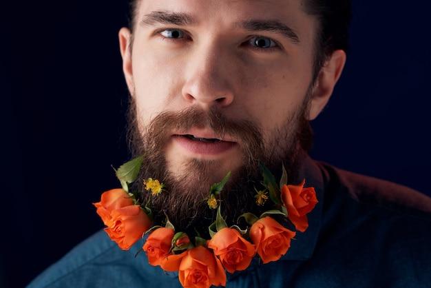 ひげの花の装飾の暗い背景を持つハンサムな男