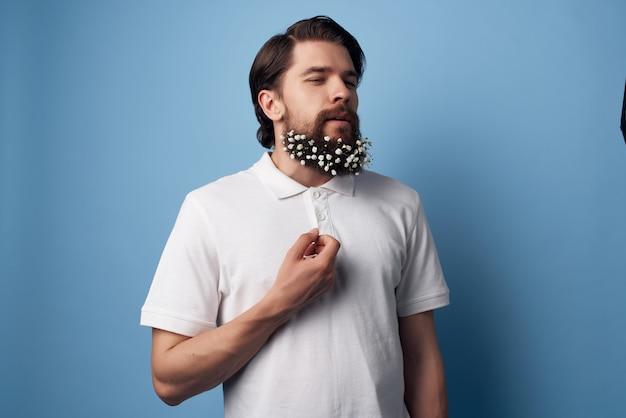 髪の白いシャツの孤立した背景にひげの花を持つハンサムな男