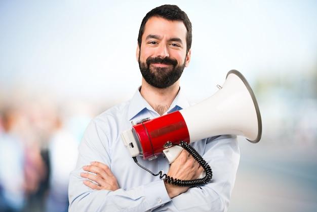 Красивый мужчина с бородой, держащий мегафон на фоне сфокусированным