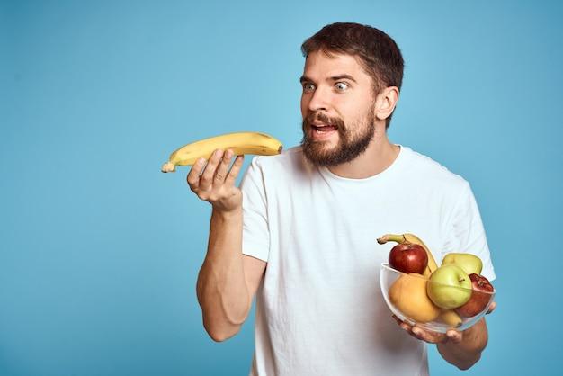 新鮮な果物を保持しているひげを持つハンサムな男