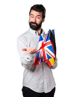 Красивый мужчина с бородкой, держащей много флагов и держащий что-то