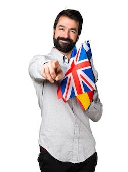 たくさんの旗を掲げて正面を指しているひげそりの男