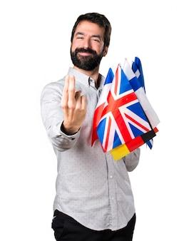 Uomo bello con la barba che detiene molte bandiere e gesto in arrivo