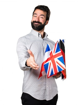 Handsome man with beard holding many flags and making a deal