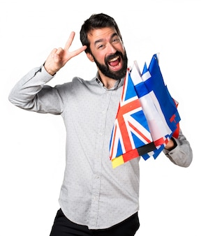 Handsome man with beard holding many flags and making victory gesture