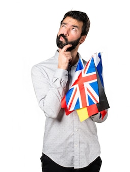 Handsome man with beard holding many flags and thinking