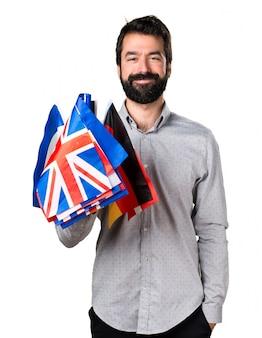 Красивый мужчина с бородой, держащий много флагов