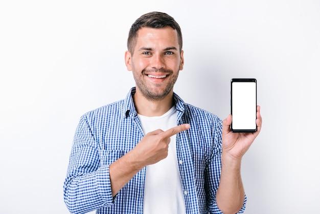스마트폰을 들고 카메라를 보면서 화면을 손가락으로 가리키는 수염을 가진 잘생긴 남자. 스튜디오 흰색 배경에 쐈 어. 사람과 기술 개념