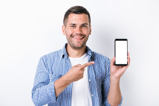 Handsome man with beard holding smartphone and pointing with the finger at the screen of it while looking at the camera. studio shot on white background. people and technologies concept