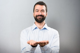Handsome man with beard holding something on textured background