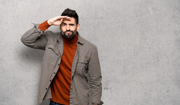 Handsome man with beard looking far away with hand to look something over textured wall
