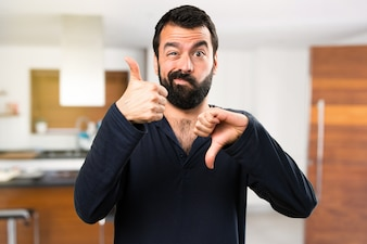 Handsome man with beard making good-bad sign inside house