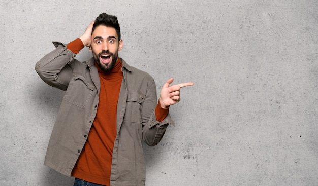 Handsome man with beard pointing finger to the side and presenting a product over textured wall