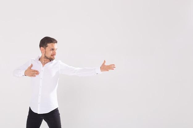 Красивый мужчина с бородой, указывая в одном направлении на белой стене, copyspace.