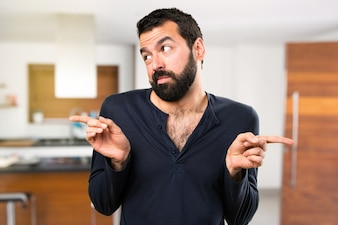 Handsome man with beard pointing to the laterals having doubts inside house