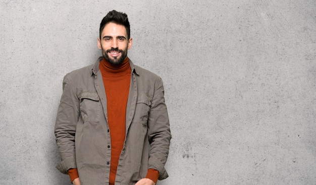 Handsome man with beard posing and laughing looking to the front over textured wall