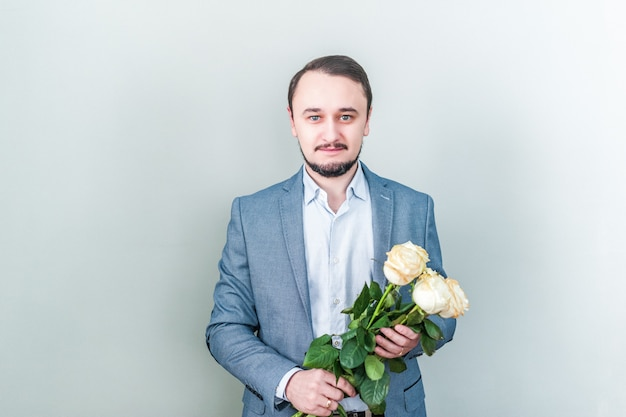 Handsome man with beard standing against a grey background with a bouquet of white roses