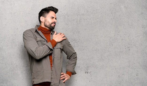 Handsome man with beard suffering from pain in shoulder for having made an effort over textured wall