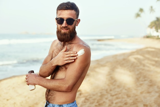 Handsome man with beard, in sunglasses sunbathing with sunscreen lotion body in summer. male fitness model tanning using solar block cream for healthy tan.