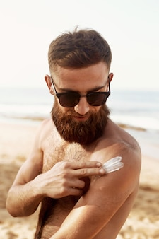 Handsome man with beard, in sunglasses sunbathing with sunscreen lotion body in summer.