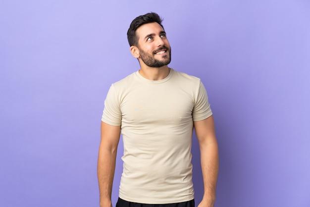 Красивый мужчина с бородой думает об идее, глядя вверх