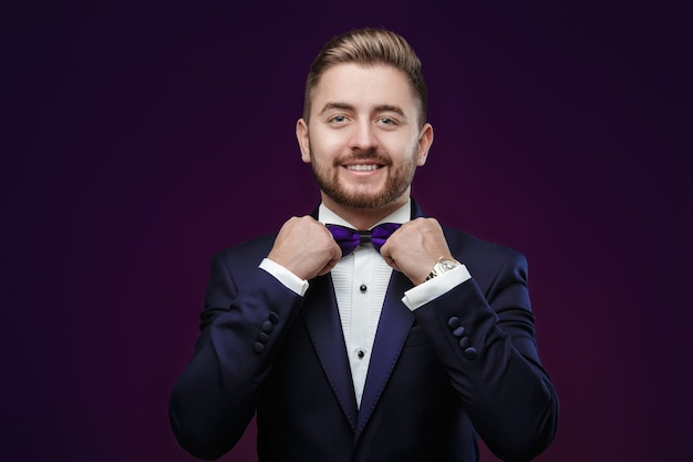 Handsome man with beard in tuxedo and bow tie looking at camera