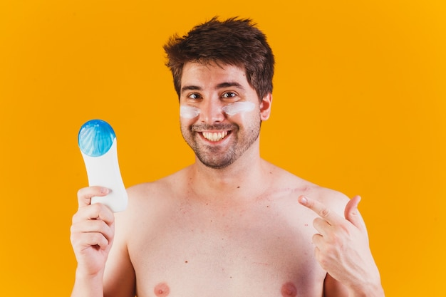 Handsome man with beard on vacation wearing swimwear holding bottle of sunscreen lotion