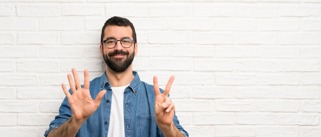 Handsome man with beard over white brick wall counting seven with fingers