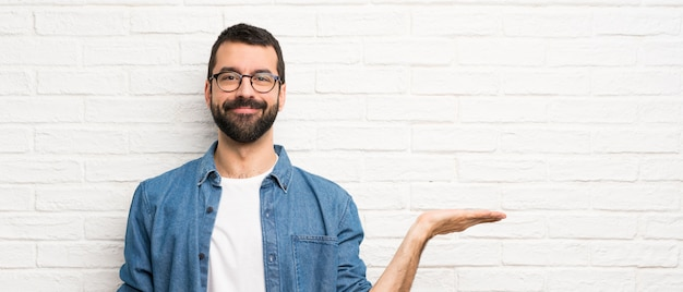 Handsome man with beard over white brick wall holding copyspace imaginary on the palm to insert an ad