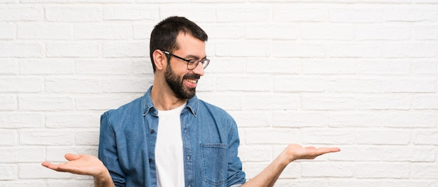 Handsome man with beard over white brick wall holding copyspace with two hands