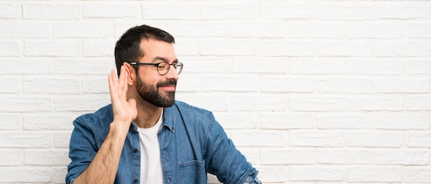 Handsome man with beard over white brick wall listening to something by putting hand on the ear