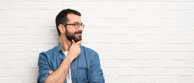 Handsome man with beard over white brick wall looking to the side