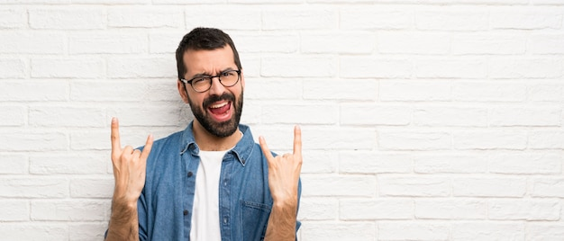 Handsome man with beard over white brick wall making rock gesture