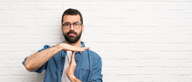 Handsome man with beard over white brick wall making time out gesture