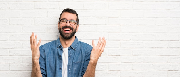 Handsome man with beard over white brick wall smiling a lot